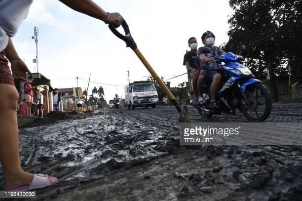 TOPSHOT A resident uses a shovel to clear mud and ash spewed by Taal volcano at a development in Tanauan town Batangas province south of Manila on...