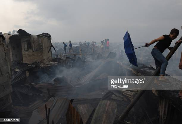 A resident uses an umbrella to avoid smoke from burning galvanized roof sheets after their homes were destroyed by a fire at an informal settlers...