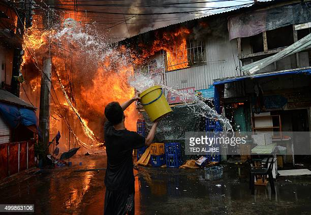 TOPSHOT A resident using a plastic container filled with water tries to put out a fire that gutted a shanty town near a jail in Manila on December 4...