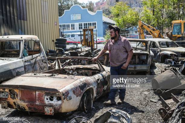 Resident Wade Holley rests his hand on his car destroyed in the Clayton Fire at the Clearlake machine shop in Lower Lake California August 16 2016 A...