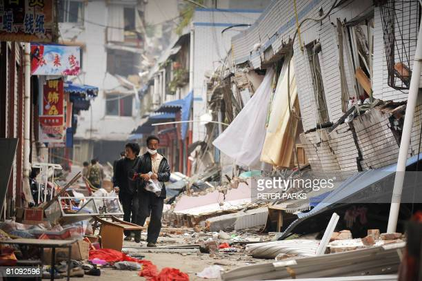 Resident walk through the debris of destroyed buildings in the town of Beichuan on May 15 2008 which has been cut off after a powerful earthquake...