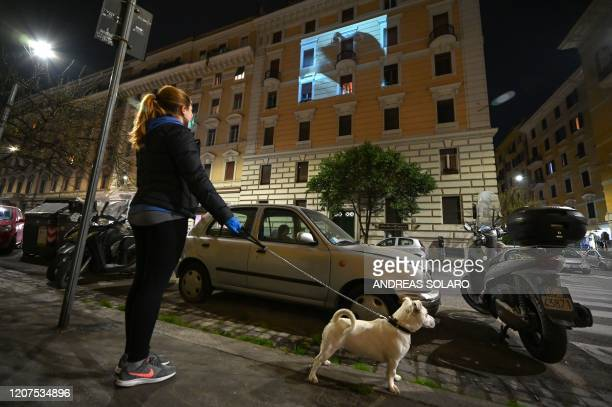 A resident walking her dog watches a film projected on the facade of a building in Rome on March 17 2020 as part of a Cinema from Home event by the...