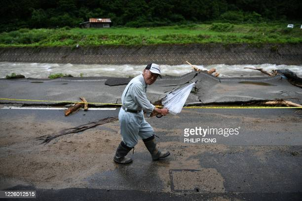 Resident walks along a damaged road by a waterway following heavy rains and flooding in the village of Takayama, Gifu prefecture on July 10, 2020. -...