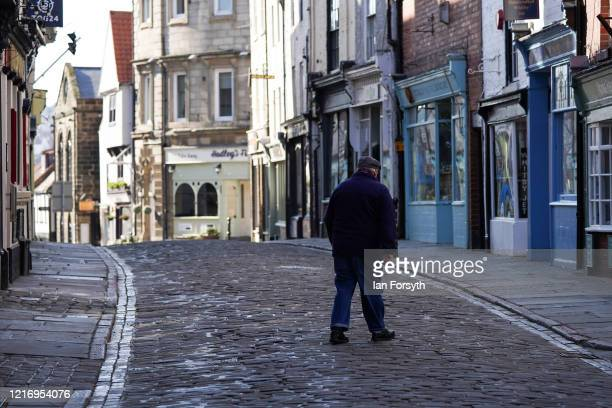 Resident walks along a deserted street in Whitby as visitors observe the guidelines during the Coronavirus pandemic lockdown on April 05, 2020 in...