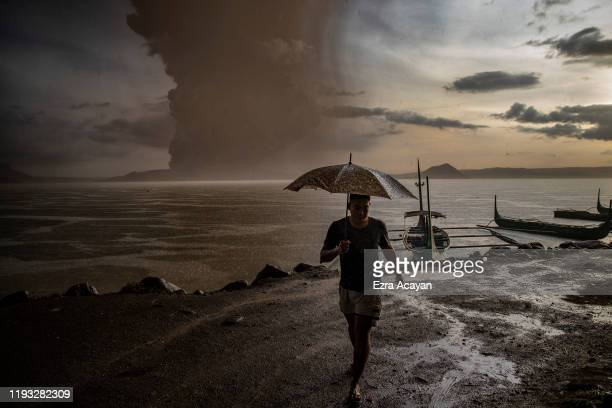 Resident walks along a lakeside as Taal Volcano erupts on January 12, 2020 in Talisay, Batangas province, Philippines. Local authorities have begun...