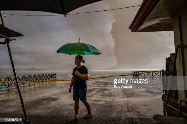 A resident walks along a lakeside as Taal Volcano erupts on January 12 2020 in Talisay Batangas province Philippines Local authorities have begun...