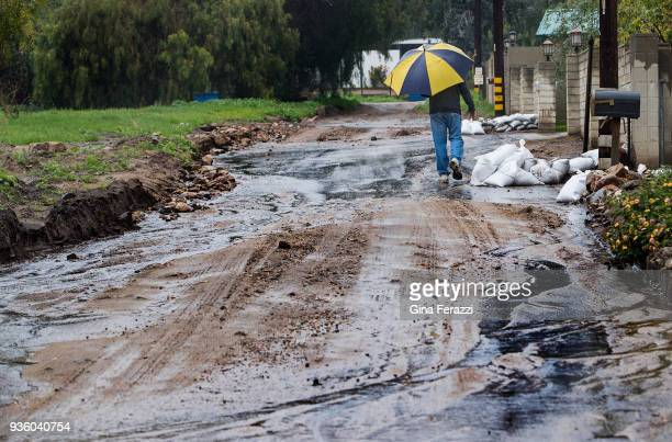 A resident walks along a mud filled street off La Tuna Canyon Road as heavy rains caused street flooding and debris flow on March 21 2018 in Sun...