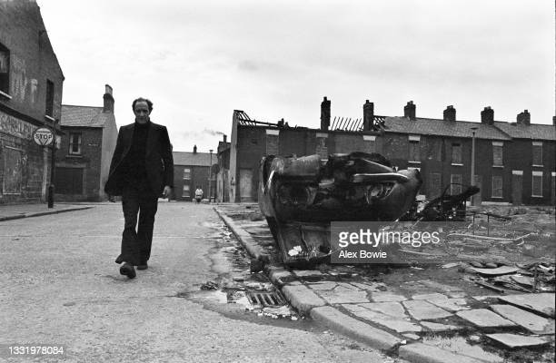 Resident walks along Hillview Street past fire-damaged derelict houses and the wreckage of burnt-out cars that lie abandoned following sectarian...