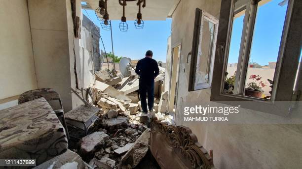 TOPSHOT A resident walks amidst the rubble of a building that was damaged when forces loyal to easternbased strongman Khalifa Haftar shelled the...
