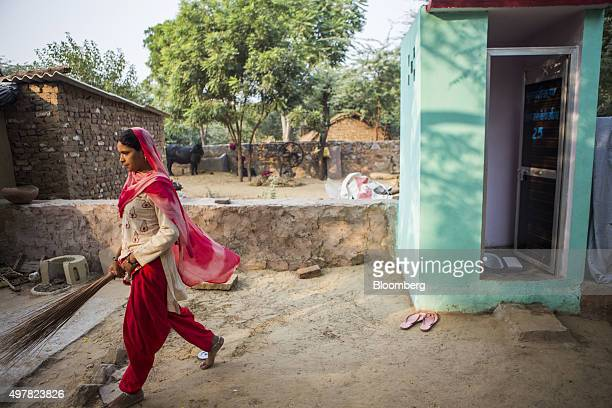 A resident walks away after cleaning a toilet block recently built by villagers with support from Sulabh International Social Service Organisation in...