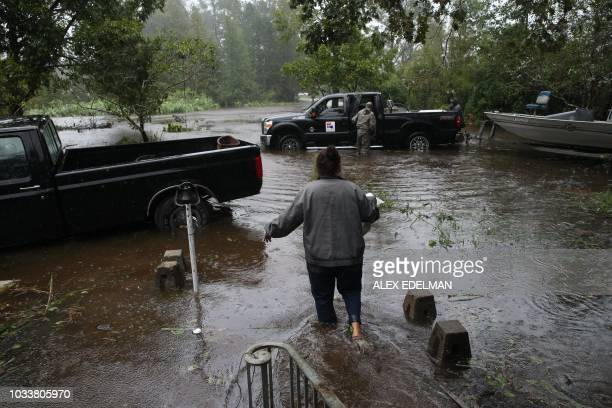 TOPSHOT A resident walks from her flooded house towards the crew of the Cajun Navy in Lumberton North Carolina on September 15 2018 in the wake of...