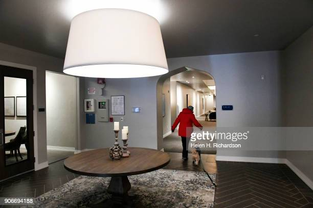 A resident walks her dog back to their condo inside the new Mirador at Tennyson condominium project inside the historic El Jebel Shrine building at...