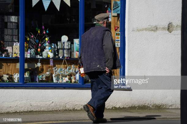 Resident walks home as the streets of Whitby remain empty of visitors observing the guidelines during the Coronavirus pandemic lockdown on April 05,...
