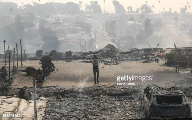 A resident walks in the remains of an apartment complex destroyed by the Thomas Fire in a residential neighborhood on December 5 2017 in Ventura...