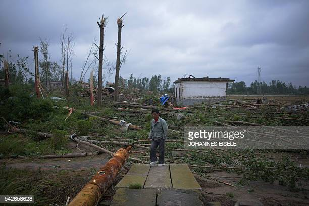 A resident walks in the rubble of destroyed houses after a tornado in Funing in Yancheng in China's Jiangsu province on June 24 2016 Extreme weather...