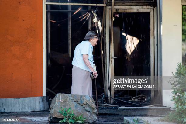 A resident walks near a burned medical center on July 4 2018 in the Breil neighborhood of Nantes following clashes between groups of young people and...