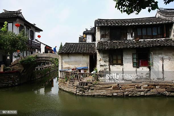 A resident walks on a bridge over a canal on August 29 2009 in Zhouzhuang Town of Kunshan City Jiangsu Province China Zhouzhuang first built around...