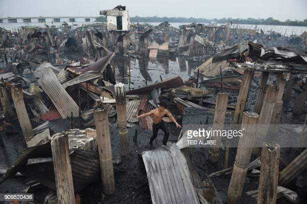 TOPSHOT A resident walks on a galvanized roof sheet and destroyed homes after a fire hit at an informal settlers area along the coast in Bacoor town...