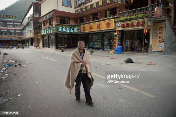 Resident walks on a street after an earthquake in Zhangzha in southwest China's Sichuan province on August 10, 2017. The 6.5-magnitude earthquake...