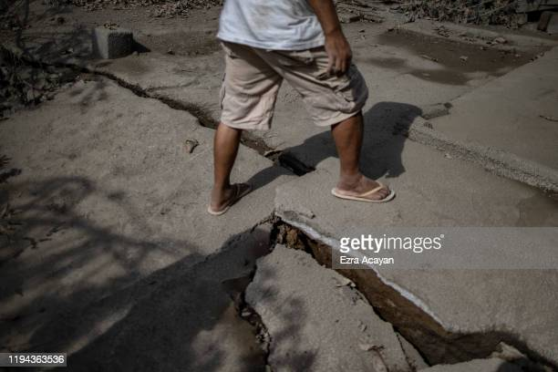 A resident walks over a fissure on the ground caused by Taal Volcano's eruption on January 18 2020 in Talisay Batangas province Philippines The...