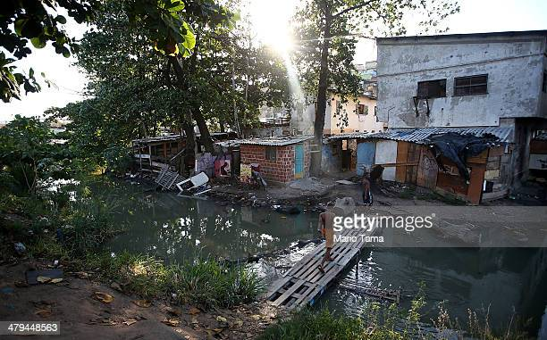 A resident walks over a makeshift bridge above a polluted stream in an impoverished area in the unpacified Complexo da Mare slum complex one of the...