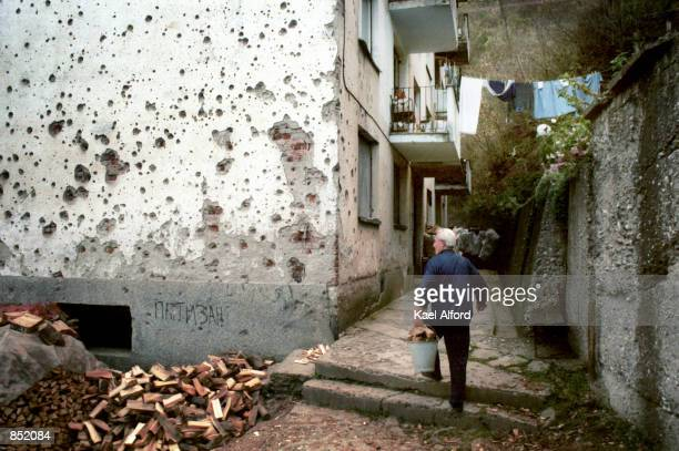 A resident walks passed a bulletscarred apartment building November 16 2000 in the wardamaged city of Srebrenica Bosnia This year marks the fifth...