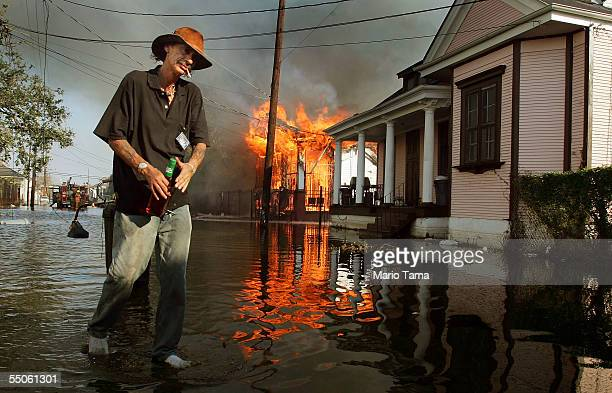 Resident walks past a burning house fire in the 7th ward September 6, 2005 in New Orleans, Louisiana. Fire companies are struggling to combat fires...