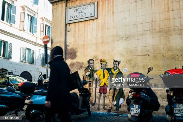 A resident walks past a mural by Italian street artist TvBoy entitled The cat and the fox Il gatto e la volpe showing Italys Labor and Industry...