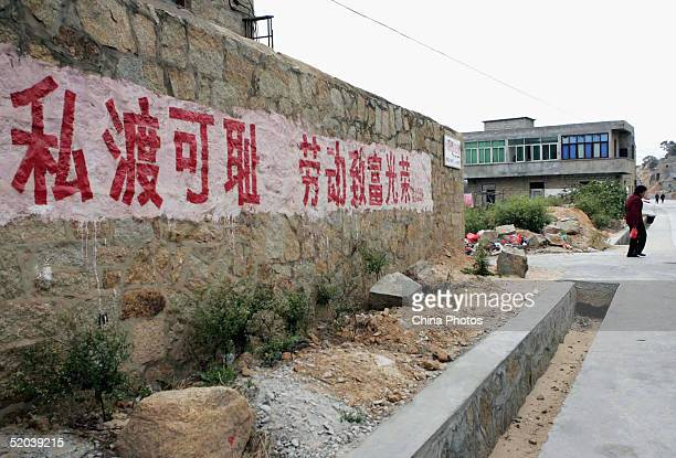 A resident walks past a wall with a slogan readingStowaway is ashamed it's honourable to get rich through work at Aodong Town hometown of the Chinese...