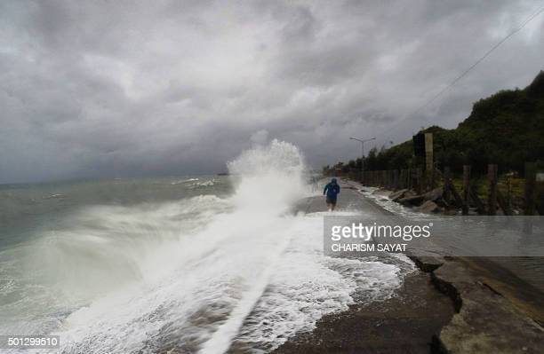 A resident walks past big waves spilling over a wall onto a coastal road in the city of Legaspi in Albay province south of Manila on December 14 as...