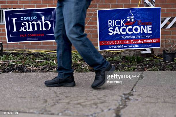 A resident walks past campaign signs for Conor Lamb Democratic candidate for the US House of Representatives and Rick Saccone Republican candidate...
