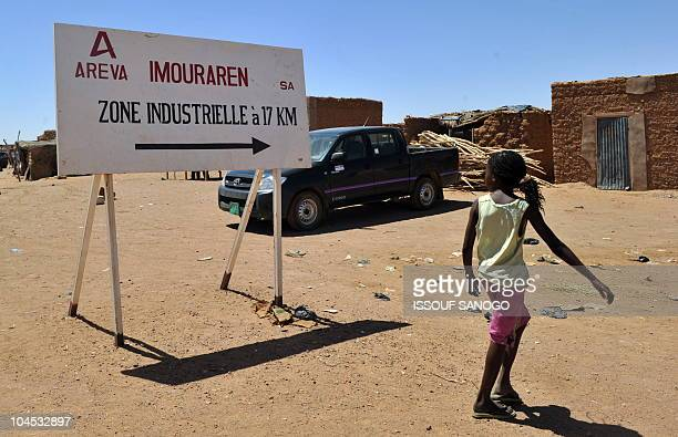 A resident walks past France's stateowned nuclear giant Areva's uranium symbol on September 27 2010 in village near Arlit Gunmen seized seven...