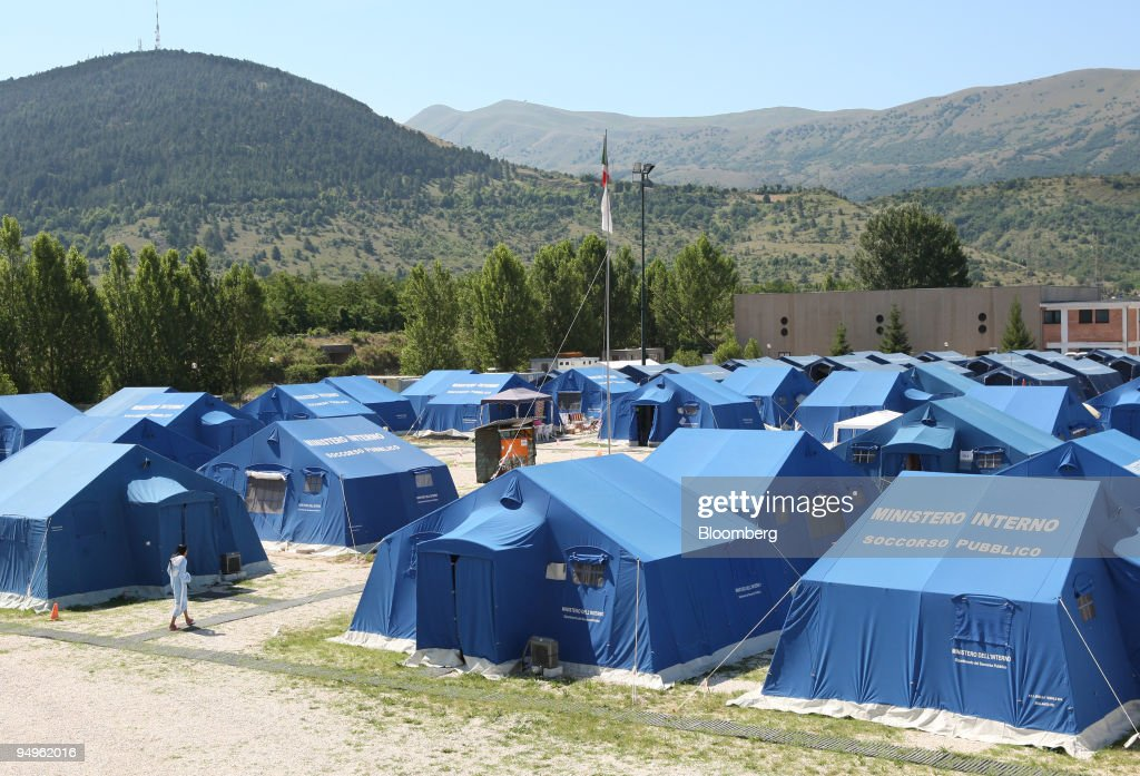 A resident walks past tents at C&o Centicolella a Red Cro & A resident walks past tents at Campo Centicolella a Red Cro ...