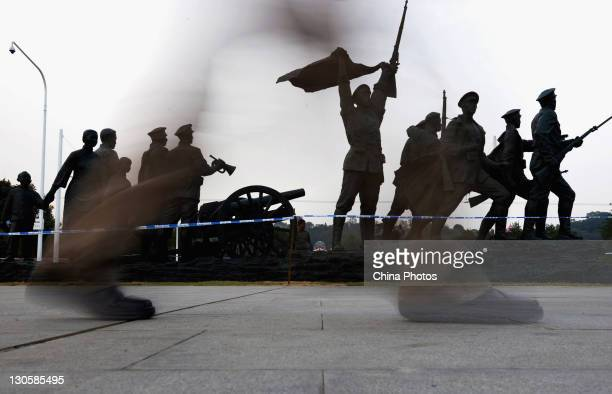 A resident walks past the group sculptures of 'The Way To The Republic' at the Wuchang Uprising Square on October 26 2011 in Wuhan of Hubei Province...