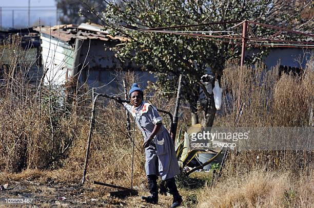 A resident walks through a gate in the township of Sharpeville south of Johannesburg on June 19 2010 AFP PHOTO / ISSOUF SANOGO