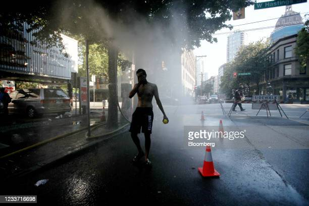 Resident walks through a temporary misting station on Abbott Street during a heatwave in Vancouver, British Columbia, Canada, on Monday, June 28,...