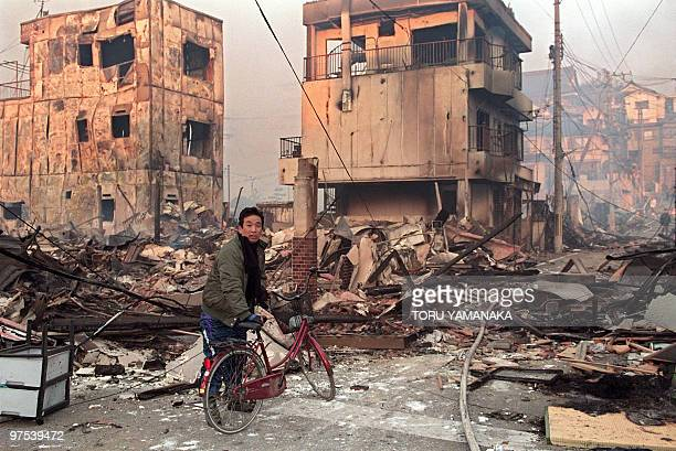 A resident walks through debris of burnt down houses 18 January 1995 in Kobe after a massive earthquake rocked Western Japan 17 January The HyogoKen...