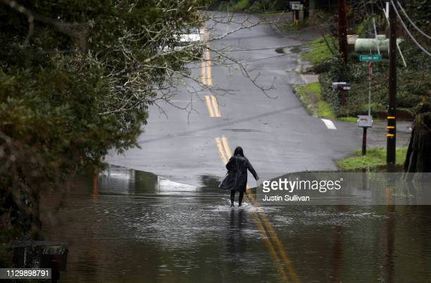A resident walks through floodwaters on February 15 2019 in Guerneville California An atmospheric river a narrow corridor of concentrated moisture in...