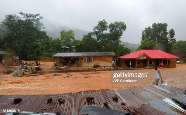 TOPSHOT A resident walks through floodwaters past a damaged building in an area of Freetown on August 14 after landslides struck the capital of the...