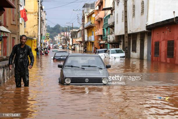 Resident walks through floodwaters past submerged vehicles on a road in Antananarivo on January 8 after heavy rainfall.