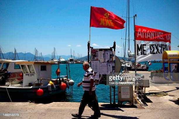 A resident walks under a fluttering flag of the Greek Communist Party at the port of the island of Aegina Greece on June 11 2012 Already faced with...