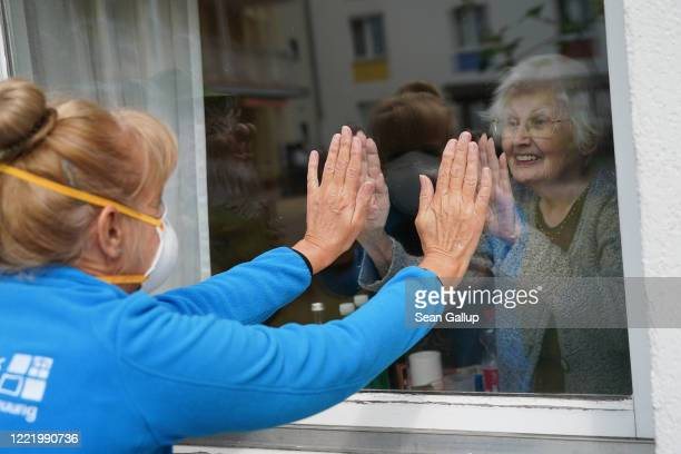 Resident Waltrud Bornschein touches the glass of her room's window to make contact with caregiver Marine Lehmberg, who is wearing a protective face...