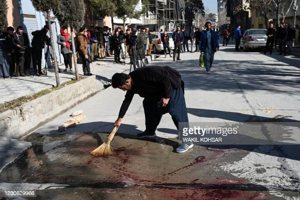 Resident washes a road following gunmen shot dead two Afghan women judges working for the Supreme Court, in Kabul on January 17, 2021. - Gunmen shot...