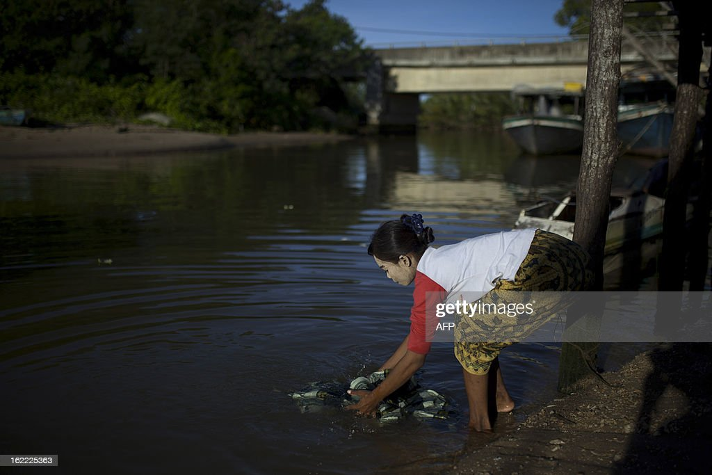 A resident washes clothes in Tanjung Labian, near the location where suspected Philippine militants are holding off on February 21, 2013. Followers of a Philippine sultan who crossed to the Malaysian state of Sabah this month will not leave and are reclaiming the area as their ancestral territory, the sultan said on February 17 amid a tense stand off.