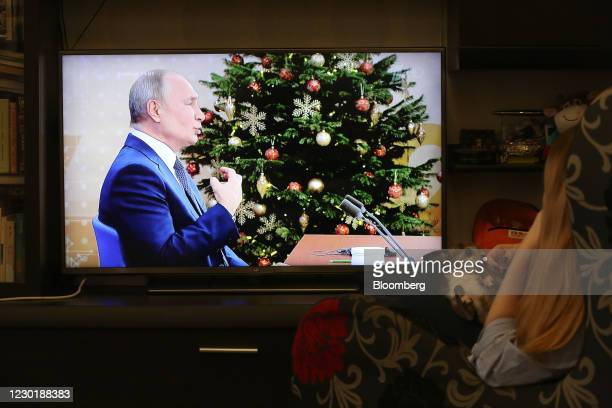 Resident watches a live broadcast of Vladimir Putin, Russia's President, delivering his annual news comference on a television in Moscow, Russia, on...