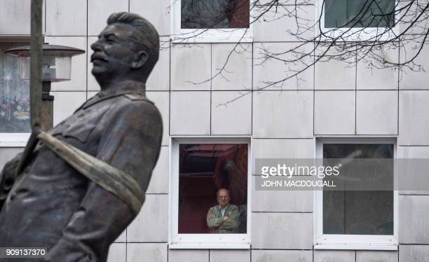 Resident watches as a 4,8-metre-high statue of former Soviet dictator Joseph Stalin is lifted by a crane on Berlin's Karl-Marx Allee on January 23,...