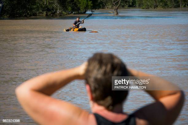 A resident watches as a property owner paddles a kayak to rescue a cow stranded in floodwaters caused by Cyclone Debbie in North MacLean Brisbane on...