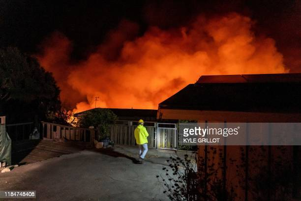 A resident watches as the Cave Fire burns a hillside near homes in Santa Barbara California early on November 26 2019 The winddriven brush fire that...