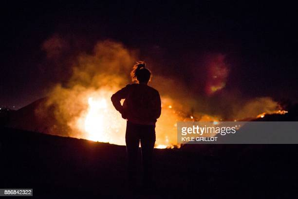 A resident watches as the Creek Fire burns along a hillside near homes in the Shadow Hills neighborhood of Los Angeles California on December 5 2017...