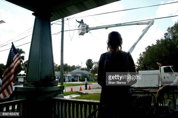 A resident watches from the porch as a crew from Florida Power Light Co works to repair a power line in the wake of Hurricane Irma on September 12...